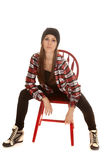 Woman in beanie and plaid shirt sit lean forward Royalty Free Stock Images