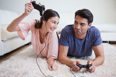 Woman beating her fiance while playing video games. In their living room Stock Photography
