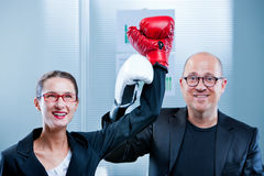 Woman beats man that admits his failure. Business women exulting after a symbolic boxe match against a plump businessman endorsing her as a winner royalty free stock photos