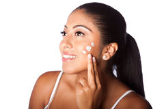Woman beaty facial moisturizing exfoliating lotion. Beautiful happy smiling woman applying facial moisturizing exfoliating lotion cream in face, isolated Royalty Free Stock Images