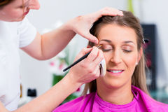 Woman with beautician in cosmetic salon. Receiving makeup stock photos