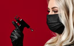 Woman beautician cosmetologist hold new popular ear piercing gun in black medical gloves and mask royalty free stock image