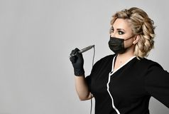 Woman beautician cosmetologist hold tattoo machine gun in black mask on gray. Background stock photos