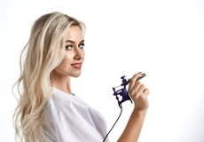 Woman beautician cosmetologist hold tattoo machine gun on white. Background stock photos
