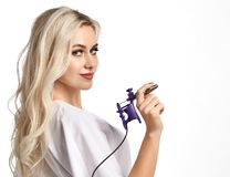 Woman beautician cosmetologist hold tattoo machine gun on white. Background stock photography