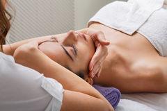 Woman beautician doctor make head massage in spa wellness center. Head and face massage in spa. Female beautician doctor with patient in wellness center Stock Image