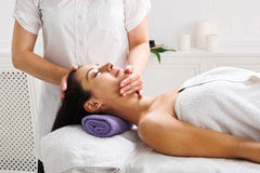 Woman beautician doctor make head massage in spa wellness center. Face lifting massage in spa. Female beautician doctor with patient in wellness center Royalty Free Stock Photography