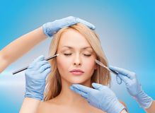 Woman and beautician hands with pencil and scalpel Stock Images