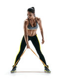 Woman with beautiful athletic body performs exercises using a resistance band. Photo of young woman isolated on white background. Strength and motivation Stock Image
