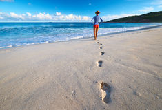 Woman at beautiful beach. Focus on footprints. Stock Image