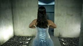 Woman in a beautiful blue dress dancing toward water at the end of corridor