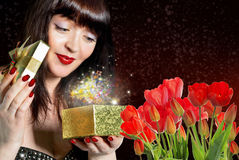 Woman with Beautiful bouquet fresh red tulips and gift Royalty Free Stock Image