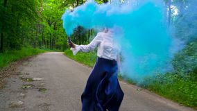 Woman in beautiful clothes runs through the forest waving colored smoke, slow motion stock footage