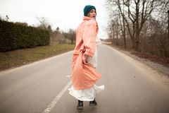 A woman in a beautiful coat and white dress rides along the way. Back viev stock photography