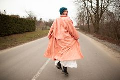 A woman in a beautiful coat and white dress rides along the way. Back viev royalty free stock photo