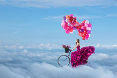 Woman in beautiful dress flying on her bike. With balloons Stock Photos