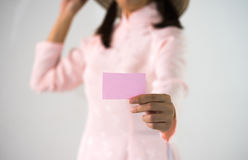 Woman beautiful dress hands holding a pink business visit card. Gift, ticket, pass, present close up on blurred white background Royalty Free Stock Photography
