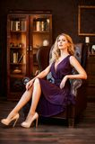 Woman in beautiful dress sits in luxury leather chair. Stunning majestic domineering woman in a beautiful dress and in high-heeled shoes sits in an expensive royalty free stock photography