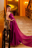 Woman in a beautiful dress sloit on the stairs Stock Images