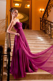 Woman in a beautiful dress sloit on the stairs Royalty Free Stock Photos