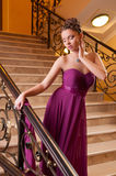 Woman in a beautiful dress sloit on the stairs Stock Photos