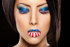 Woman beautiful face with perfect makeup. On black backround. on the lips and eyes painted an American flag Royalty Free Stock Photo