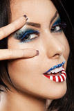 Woman beautiful face with perfect makeup. On black backround. on the lips and eyes painted an American flag Royalty Free Stock Photography