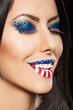 Woman beautiful face with perfect makeup. On the lips and eyes painted an American flag Stock Photography