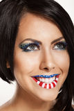 Woman beautiful face with perfect makeup. On the lips and eyes painted an American flag Royalty Free Stock Photo