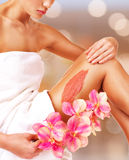 The woman with a beautiful with flowers body using a scrub royalty free stock photography