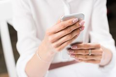 Woman with beautiful french manicure using smartphone stock photography
