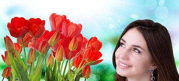 Woman with Beautiful garden fresh red tulips Stock Photos