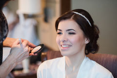 Woman with beautiful hairstyle doing makeup Stock Photo