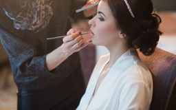 Woman with beautiful hairstyle doing makeup. Boudoir Stock Images
