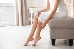Woman with beautiful legs and feet sitting on ottoman indoors, closeup with space for text. Spa treatment stock photo
