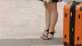 Woman with beautiful legs in high heel shoes waiting for train, bus station. Stock footage stock images