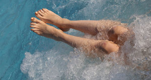 Woman with beautiful legs in the pool with whirlpool of luxuriou stock photo