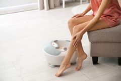 Woman with beautiful legs sitting near foot bath at home, closeup with space for text. Spa treatment stock images