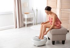 Woman with beautiful legs using foot bath at home. Space for text. Spa treatment royalty free stock photo