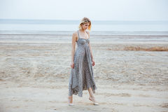 Woman in beautiful long dress walking tiptoes on the beach Stock Photos
