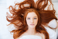 Woman with beautiful long red hair lying in bed Royalty Free Stock Photos