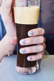 Woman with beautiful manicure holds a cold coffee Royalty Free Stock Images