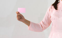 Woman beautiful pink dress hands holding a pink business visit card. On white background royalty free stock photos