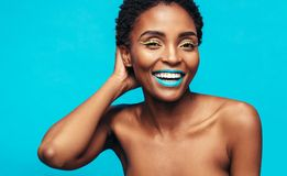 Woman with beautiful skin and vivid makeup. African woman with beautiful skin and vivid makeup. Portrait of attractive female model looking at camera and smiling Royalty Free Stock Photos