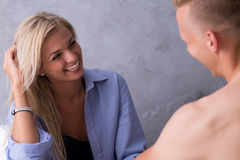 Woman with a beautiful smile. Woman in blue man's shirt smiling at the young man Stock Images