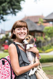 Woman beautiful young happy with poppy beagle holding a dog in her hands. Balinese temple backgorund. Indonesia, Bali. Woman beautiful young happy with poppy Stock Photo