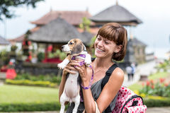 Woman beautiful young happy with poppy beagle holding a dog in her hands. Balinese temple backgorund. Indonesia, Bali. Woman beautiful young happy with poppy Royalty Free Stock Photos