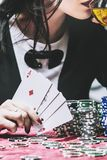 Woman beautiful young successful gambling in a casino at a table. With cards, chips and alcohol closeup royalty free stock photos