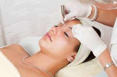 Woman beautifying herself in beauty spa. Young woman getting beauty treatment in wellness center Royalty Free Stock Photo