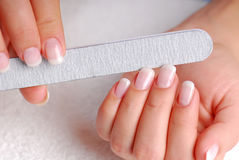 Woman beauty. Polishing of nails with the nailfile Stock Image
